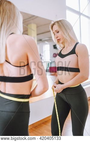 Beautiful Blonde Woman Measuring Her Athletic Fit Abdomen With Yellow Tape. Successful Weight Loss C