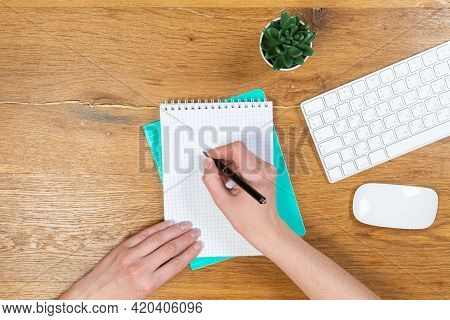 Workspace With A Keyboard, Girl's Hands Writes In A Notebook On A Wooden Table, Top View Of An Offic