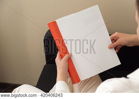 Beautiful Female Hands Hold An Open Book Or Magazine In A Room On A Black Sofa