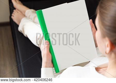 Woman Holding Brochure With Blank Cover On Wooden Background, Top View. Mock Up For Design