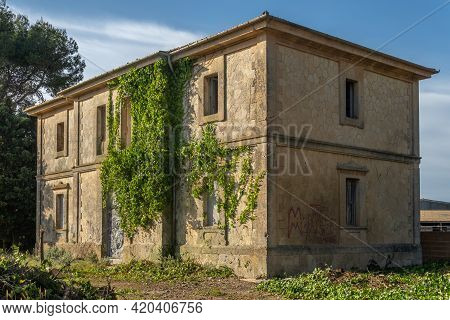 Building Of The Old Treian Station In The Town Of Porreres Abandoned With Ivy On Its Facade On A Sun