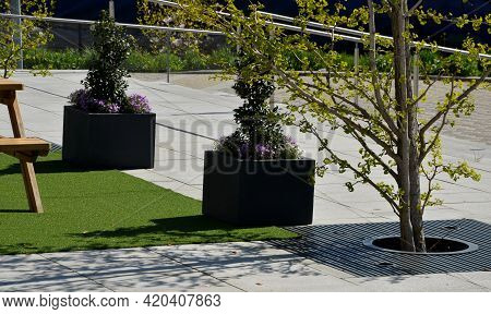 Two Gray Flower Pots At The Park Seating On The Terrace With An Artificial Plastic Carpet Reminiscen
