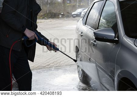 A Man Uses A High-pressure Washer To Wash Off The Foam From The Bottom Of The Doors Of A Gray Car At