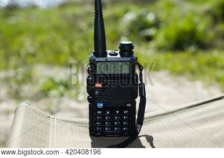 Black Walkie-talkie Close-up Stands On Cloth Stool Against Background Of The River. Concept Of Commu