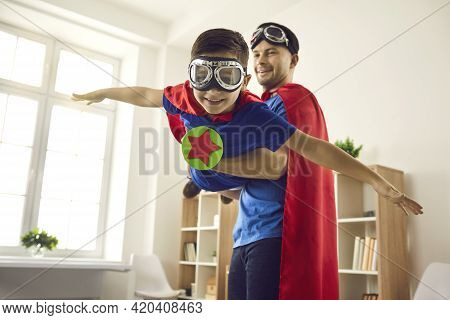 Cheerful Father And Preschool Son Playing In Superhero In Living-room At Home