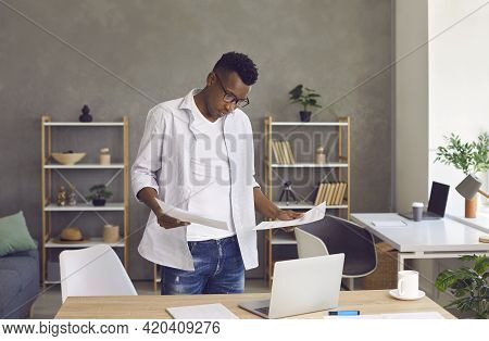 Serious African American Man Doing Business Paperwork And Using Laptop In His Home Office