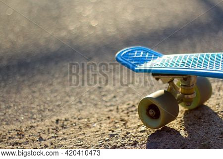 Defocus Close Up Blue Skateboard On Morning At Park. Head Of Skateboard And Wheel On Road At Public