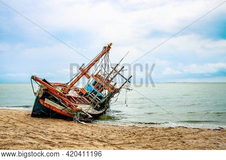 The Old Wrecked Fishing Boat On The Beach.