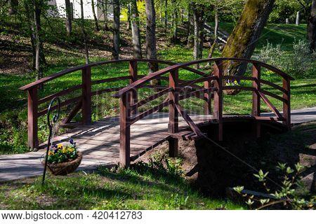 Red Wooden Bridge For Pedestrians Over A Small Park River. Widow's Flower Pot Next To The Bridge.