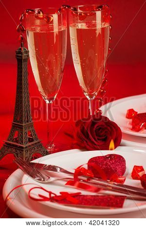 Image of red luxury table setting, white festive plate and two glass of champagne decorated with small Eiffel tower and fresh rose flower, dinner in Paris, honeymoon in France, Valentine day