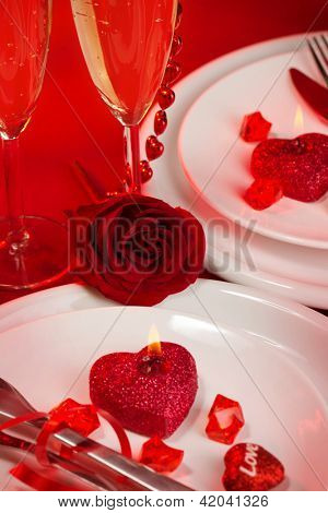 Picture of beautiful holiday table setting, white festive plates with wine glasses on red luxury tablecloth, romantic dinner in restaurant, Valentines day, wedding banquet, romance and love concept