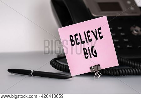 The Text Believe Big Written On A Pink Sticky Note To Remind You An Important Event. Closeup Of A Pe