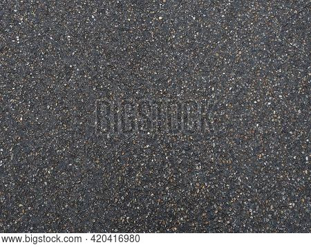 Dark Pavement With A Grainy Pockmarked Texture. Full Screen Photo. Background Texture