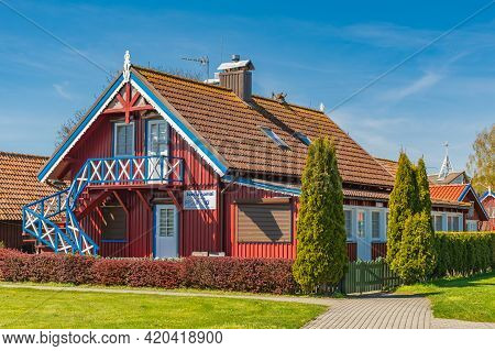 Nida, Lithuania - May 10 2021: Beautiful Old Lithuanian Traditional Wooden Red House Of The Curonian