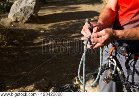 A Male Climber Ties A Safety Knot Eight On The Harness Before Climbing The Track. Climbing Equipment
