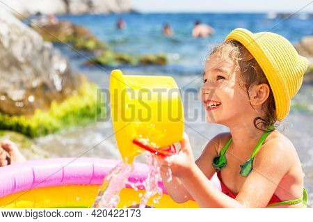 Girl In Yellow Straw Hat Plays In Outdoor Near Sea, In Water With A Bucket In An Inflatable Pool On