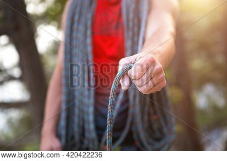 A Male Climber Of Caucasian Appearance With A Coiled Rope In His Hand. Rope Winding, Knot, Equipment