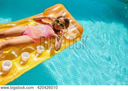 Little Girl In Sunglasses Relaxing In Swimming Pool, Enjoying Suntans, Swims On Inflatable Yellow Ma