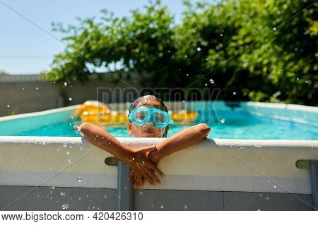 A Cute Happy Young Girl Child Playing In Swimming Pool Wearing Blue Diving Mask