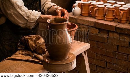 Potter Hands Making In Clay On Pottery Wheel. Potter Makes On The Pottery Wheel Clay Pot. Authentic