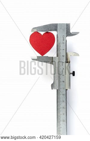 A Caliper Measures The Heart On A White Background. Measuring The Heart With An Instrument. Measure