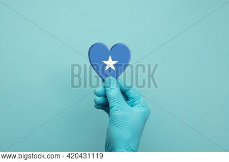 Hands Wearing Protective Surgical Gloves Holding Somalia Flag Heart