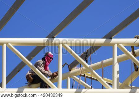Asian Construction Worker Is Welding Metal On Top Of Building Roof Structure Against Blue Sky Backgr