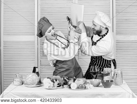 Couple In Love Cooking Healthy Recipe. Couple Fight For Book Recipes. Improve Cooking Skill. Book Re