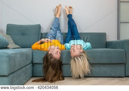 Two Happy Young Female Sisters Are Lying On The Sofa, Legs Up, Hair Down, Looking At Each Other. Con