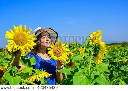 Piece Of Nature. Cheerful Child In Straw Hat Among Yellow Flowers. Small Girl In Summer Sunflower Fi