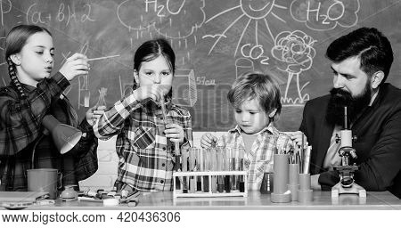 Teacher And Pupils Test Tubes In Classroom. Chemistry Themed Club. Interests And Topic Club. Group I