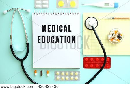 A Notebook With The Text Medical Education Is Neatly Folded Among The Pills, A Stethoscope, And A Ye