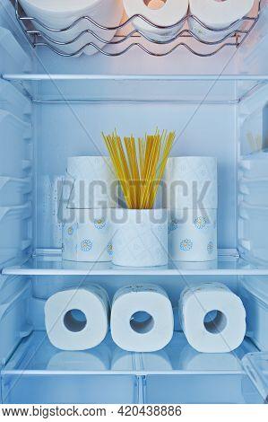 Rolls Of Toilet Paper And Spaghetti On Shelves In Fridge