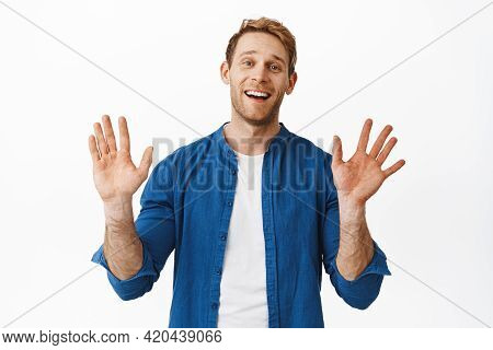 Bye Hello. Smiling Handsome Young Man Waving Hands And Looking Friendly, Say Farewell Goodbye Or Hi,