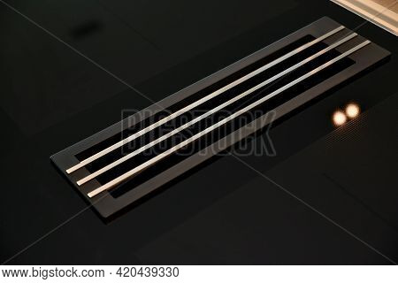 From Above Of Chrome Grid Covering Vent Duct In Floor Reflecting Lamp Ligh
