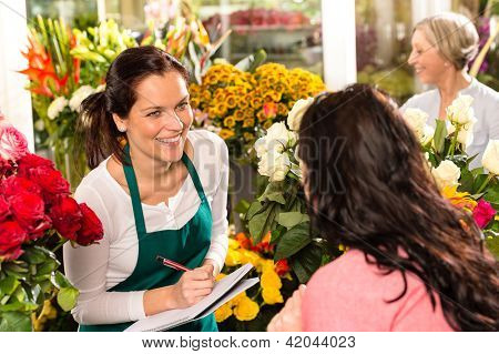 Happy florist writing flower shop talking customer woman