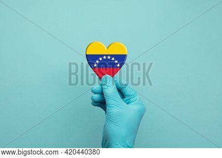 Hands Wearing Protective Surgical Gloves Holding Venezuela Flag Heart
