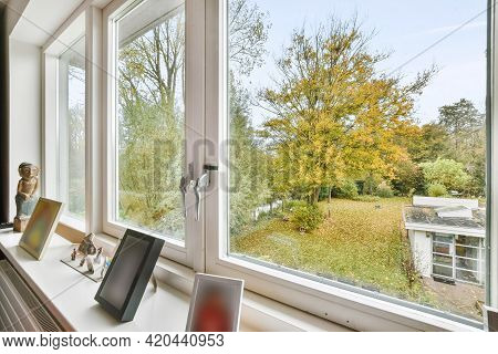 Wet Balcony With Opened Window And Glass Fence Viewing Road With Car And Green Fields Of Rural Land