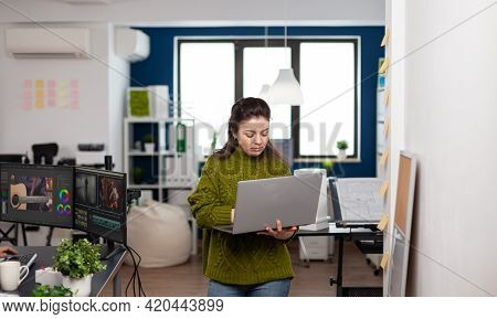 Employee Holding Laptop Standing In Creative Agency Office Prosessing Customer Video Project In Post