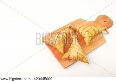 Ketupat Palas Or Rice Dumpling On Wooden Board. Ketupat Palas Is A Natural Rice Casing Made From You