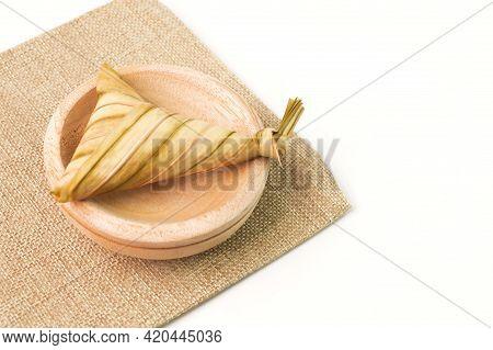 Ketupat Palas Or Rice Dumplingon Wooden Plate. Ketupat Palas Is A Natural Rice Casing Made From Youn
