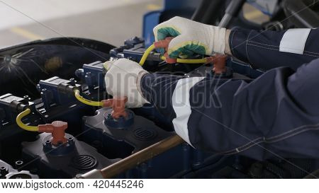 Close Up Of A Worker Changing Spark Plugs Of A Truck At The Repair Center. Scene. Mechanic Performin