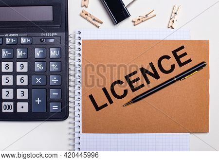 On The Desktop Is A Calculator, A Pen And Clothespins Near A Notebook With The Text Licence. Busines