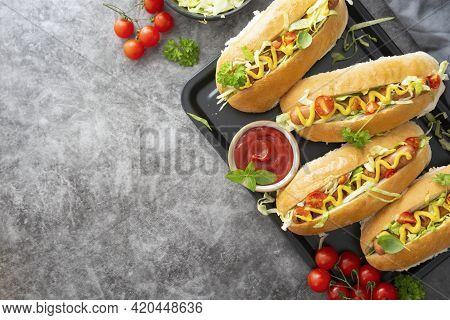Homemade Hot Dog Sandwiches. Hot Dogs With Mustard And Letuce Toping On Dark Background