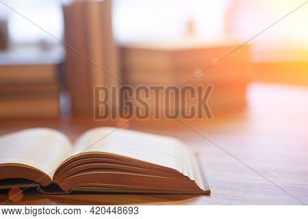 Book Background. Blurred Open Book On A Table In A University Or School Library In The Sunlight From
