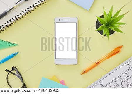 Vertical Mobile Phone Or Smart Phone Mock Up On Office Desk Or Office Table With Office Supplies As