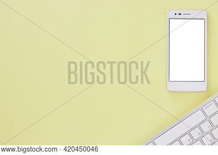 Top View Or Flat Lay White Mobile Phone Mock Up And Computer Keyboard On Office Desk Or Office Table