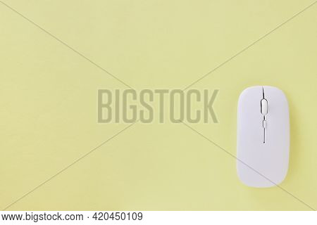 Top View Or Flat Lay White Mouse On Office Desk Or Office Table Background. Pastel Yellow Workspace