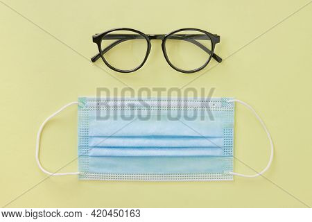 Top View Black Glasses And Blue Face Mask On Pastel Yellow Minimalist Background