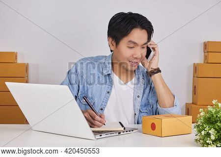 Online Merchant Or Casual Businessman In Online Store Using Smartphone And Writing Note And See Cust